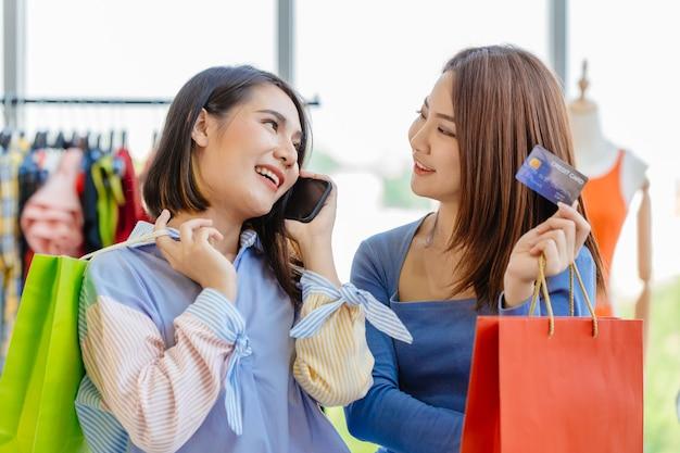 Aziatische meisjes genieten van winkelen met contant geldloze creditcardtelefoonlening van callcenterbetaling met vriend gelukkig moment plezier in uitverkoop winkel samen.