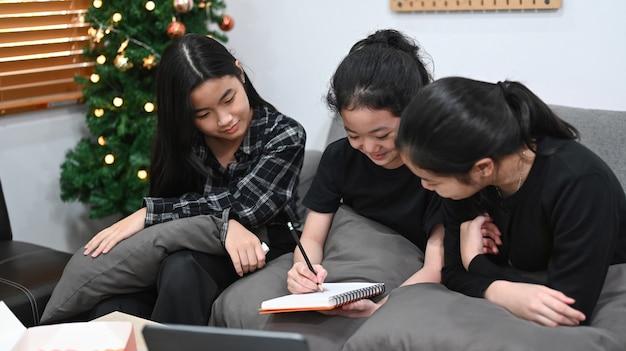 Aziatische meisjes leren online in virtuele klas met leraar-tutor op laptop.