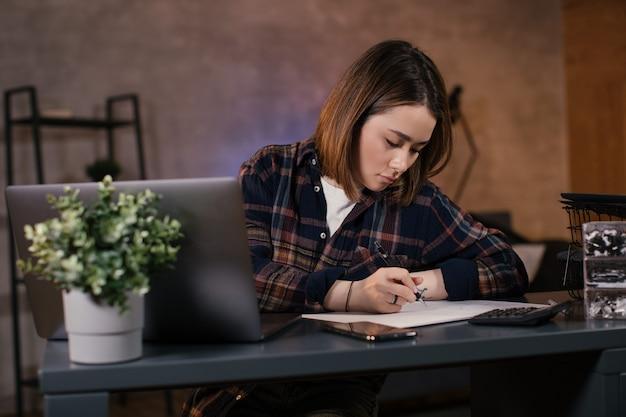 Aziatische meisjeshandelaar die aan laptop thuis werkt