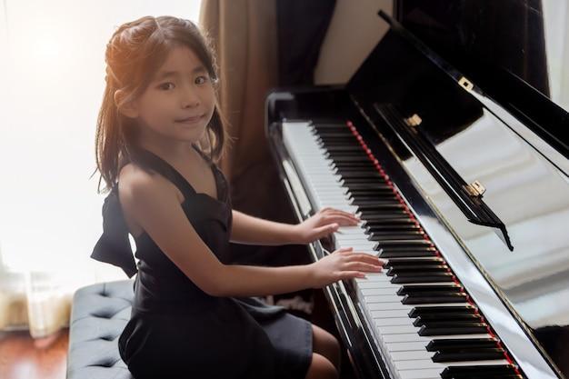 Aziatische meisjeskinderen die piano spelen, hebben talent en oefenen voor vaardigheid