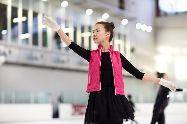 Aziatische meisjeskunstschaatsen in ijsbaan