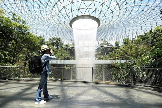 Aziatische meisjesreiziger die met rugzak met het houden van dslr-camera in zijn handen genieten van het spreken van beelden aan mooie regenwerveling op de luchthaven van juweel changi in singapore