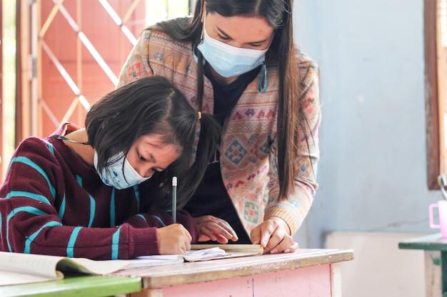 Aziatische meisjesstudenten die in klaslokaal studeren.