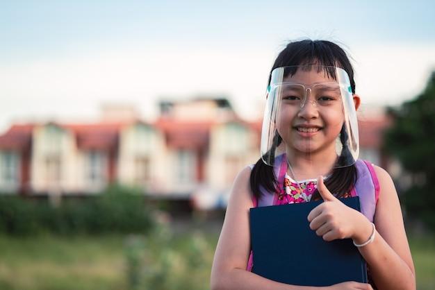 Aziatische meisjestudent die gezichtsschild draagt tijdens zij die terug naar school na quarantaine covid-19 gaat.