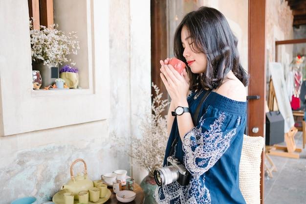Aziatische meisjesvrouwen ruiken theekop