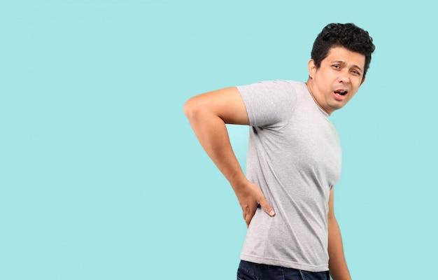 Aziatische mens die aan rugpijn, lage rugpijn op lichtblauwe achtergrond in studio lijden