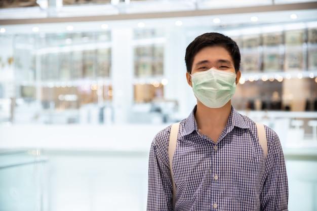 Aziatische mens die achter medisch beschermend masker in nieuw normaal levensstijlconcept glimlacht.