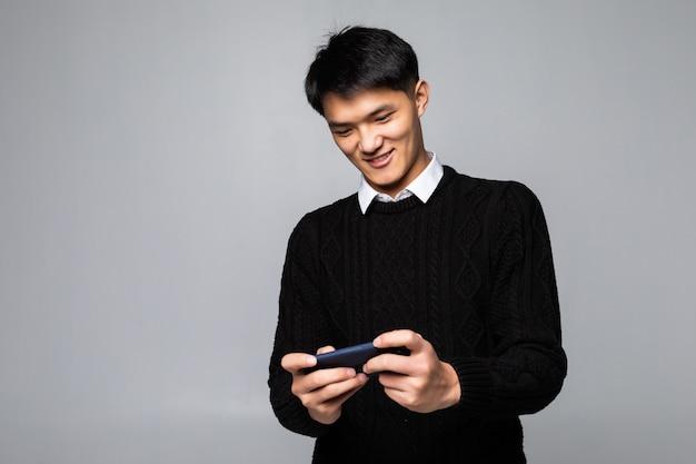 Aziatische mens die cellphone voor het spelen van spel gebruiken dat op grijze muur wordt geïsoleerd