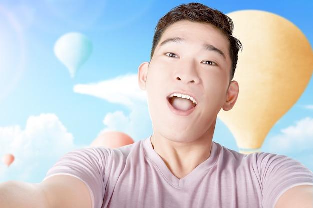 Aziatische mens die een selfie met kleurrijke luchtballon neemt die met blauwe hemelachtergrond vliegt
