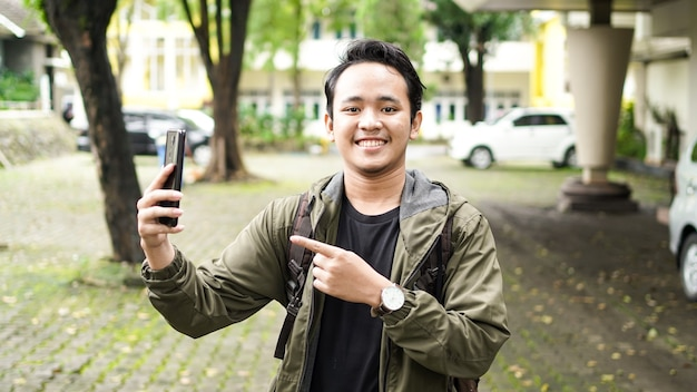 Aziatische mens die een zak draagt die de telefoon richt