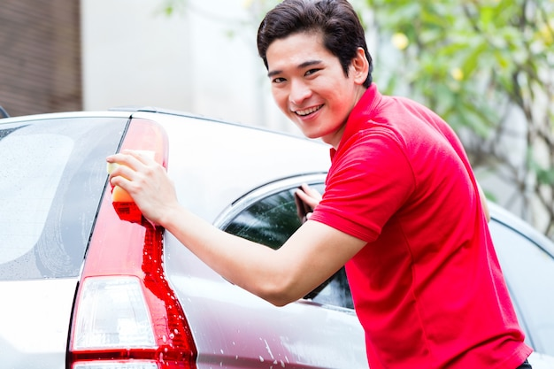 Aziatische mens die en auto met spons schoonmaken wassen