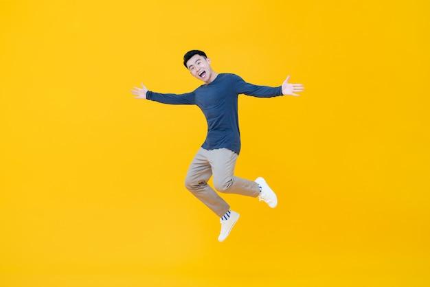 Aziatische mens die en met uitgestrekte wapens glimlacht springt