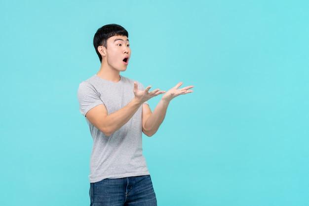 Aziatische mens die handen met geschokt gezicht opheffen