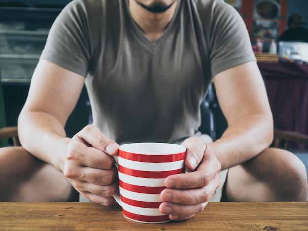 Aziatische mens die hete koffiecacao of thee op houten lijst drinkt.