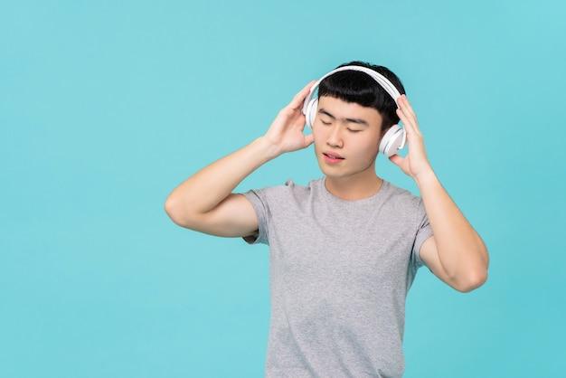 Aziatische mens die hoofdtelefoons draagt die aan emotionele muziek luisteren