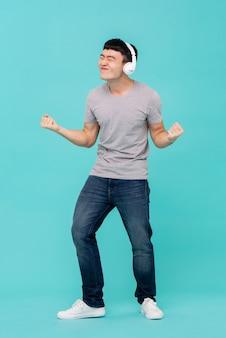 Aziatische mens die hoofdtelefoons draagt die aan muziek luisteren