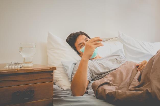 Aziatische mens die in bed ligt dat beschermend masker draagt en temperatuur meet