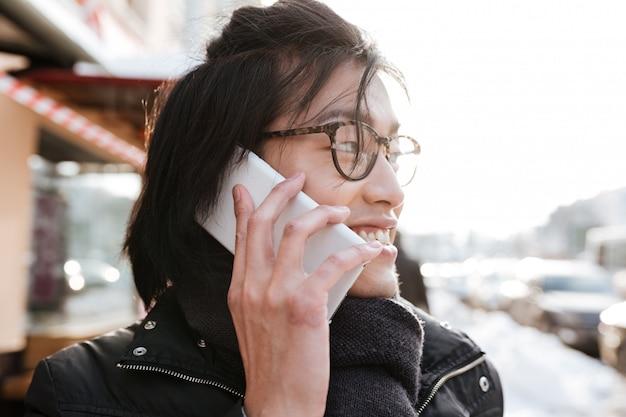 Aziatische mens die in openlucht terwijl het spreken telefonisch loopt.