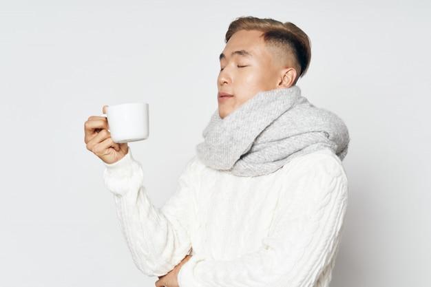 Aziatische mens die in warme de winterkleren een hete thee drinkt