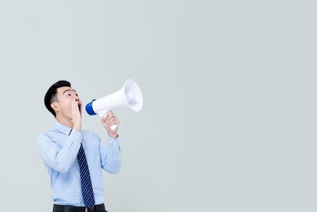 Aziatische mens die in zaken attrie op megafoon schreeuwt