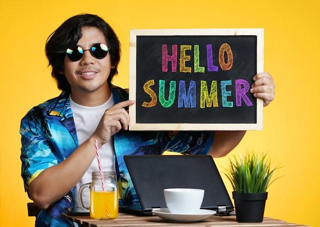 Aziatische mens die leeg bord houdt terwijl het werken aan het seizoen van de zomervakantie tegen gele achtergrond