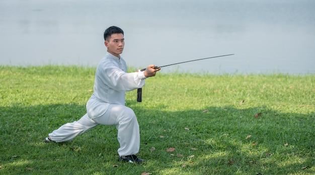 Aziatische mens die met tai chi-zwaard in de ochtend bij het park, chinese vechtsporten, gezonde zorg voor het levensconcept uitwerken.