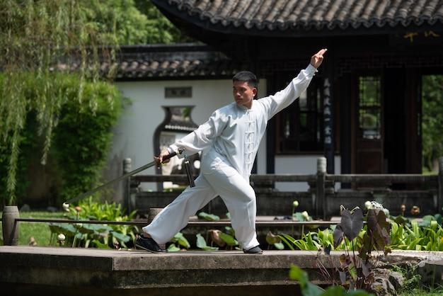 Aziatische mens die met tai chi-zwaard in de ochtend bij het park, chinese vechtsporten uitwerken