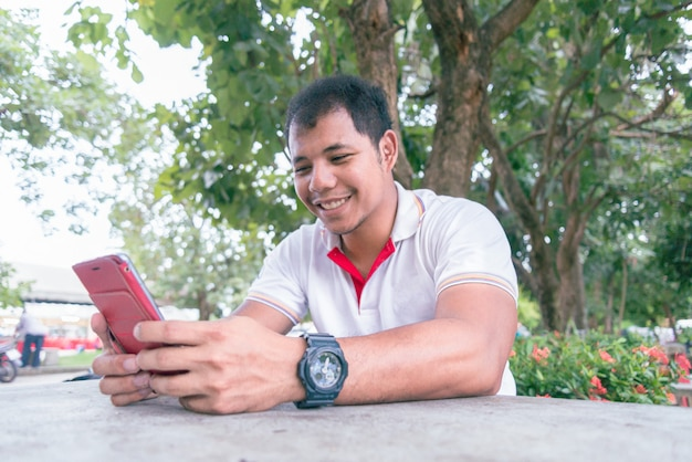Aziatische mens die op middelbare leeftijd mobiele telefoon op de lijst in het park dichtbij de avondtijd gebruiken. hij kijkt gelukkig ogenblik. concept ontspannen mensen die mobiele apparaten werken.