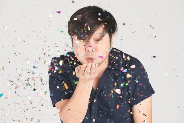 Aziatische mens die pret met kleurrijke confettien op grijs heeft.