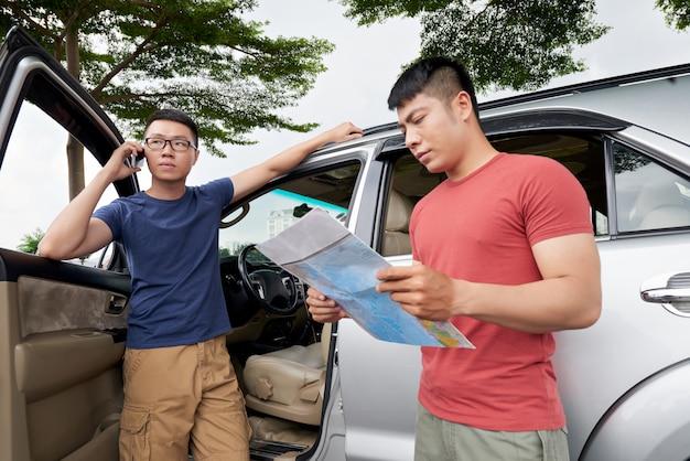 Aziatische mens die zich door zijn auto bevindt en op telefoon en vriend spreekt die kaart controleert
