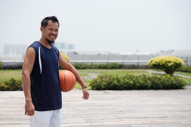 Aziatische mens die zich in openlucht bij stadion bevindt, basketbal en het glimlachen houdt