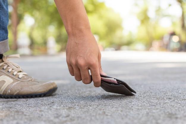 Aziatische mens die zwarte portefeuille op de weg in toeristische attractie plukt