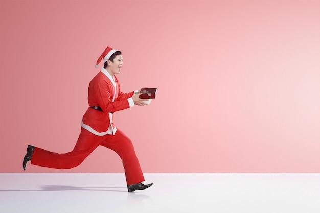 Aziatische mens in kerstmankostuum die terwijl het houden van de giftdoos lopen