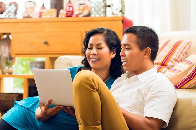 Aziatische mensen die notitieboekje het lachen zitten