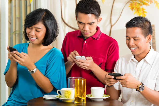 Aziatische mensen die pret met mobiele telefoon hebben