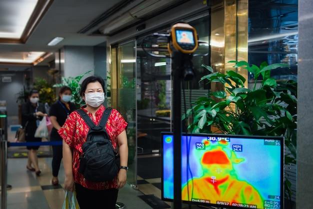 Aziatische mensen die wachten op lichaamstemperatuurcontrole voordat ze het gebouw betreden met een thermoscan of infrarood thermische camera