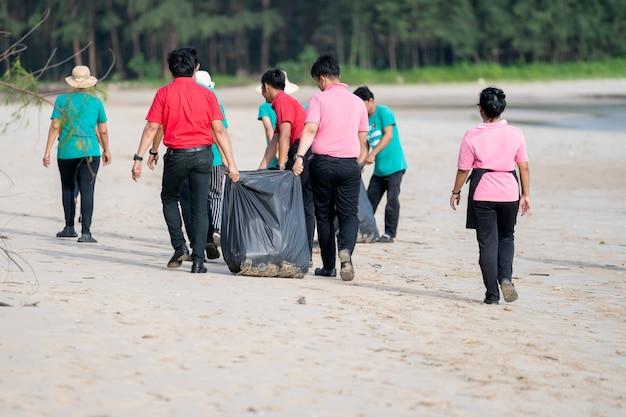 Aziatische mensen die wit zandstrand schoonmaken
