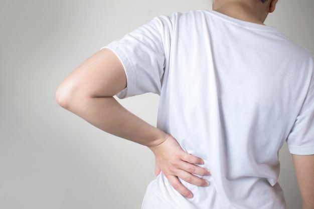 Aziatische mensen dragen witte t-shirts en voelen rugpijn.