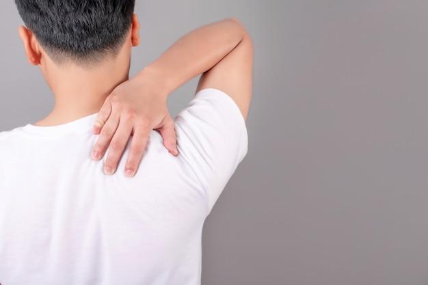 Aziatische mensen dragen witte t-shirts met schouderpijn en gebruiken hun handen om de schouders op een grijze achtergrond aan te raken.