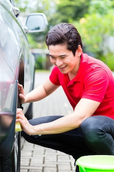 Aziatische mensen schoonmakende auto randen met spons