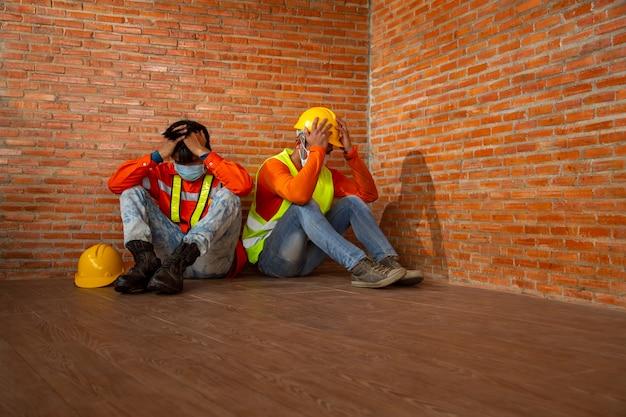 Aziatische mensen stopzetting van de bouwwerkzaamheden als gevolg van de uitbraak van de ziekte van coronavirus 2019 of covid-19. concept van economische crisis, werkloosheid bouwvakker.