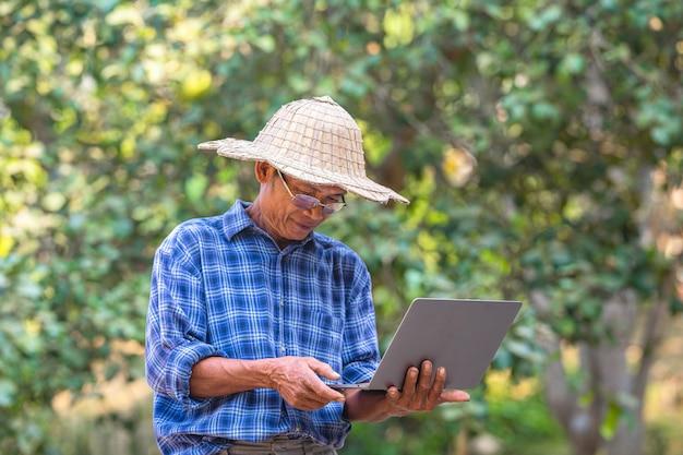 Aziatische mensenboer met slim telefoon en laptop bedrijfs en technologieconcept, aziatische mensenlandbouwer op lege exemplaarruimte