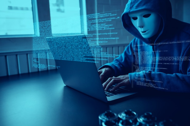 Aziatische mensenhakker draagt een masker met behulp van een laptop cyberaanval.