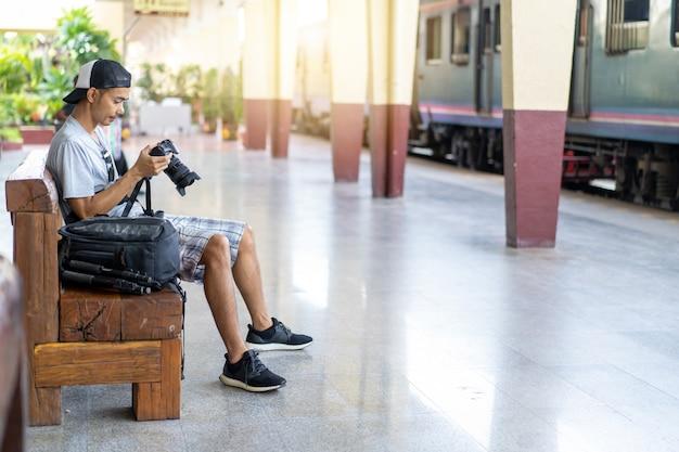 Aziatische mensenreiziger met het houden van fotocamera en rugzak bij station