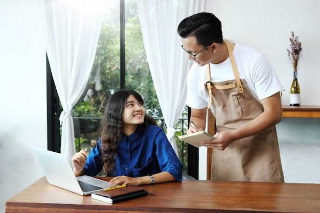 Aziatische mensenserveerster die orde van vrouw in de koffie nemen