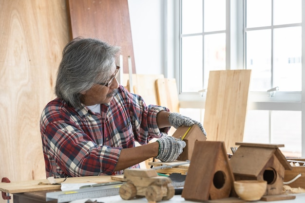 Aziatische mensentimmerman die aan houtbewerkingslijst werken in de winkel van het huistimmerwerk