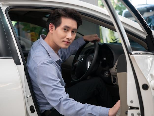 Aziatische mensenzitting in nieuwe auto en het tonen van autosleutels. jonge aantrekkelijke de salonauto die van de mensenzitting uit open venster kijkt.