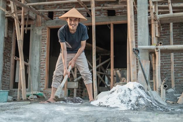 Aziatische metselaar die een schoffel voor deeg voor zand en cement voor gebouwen houdt tegen de achtergrond van een woningbouw