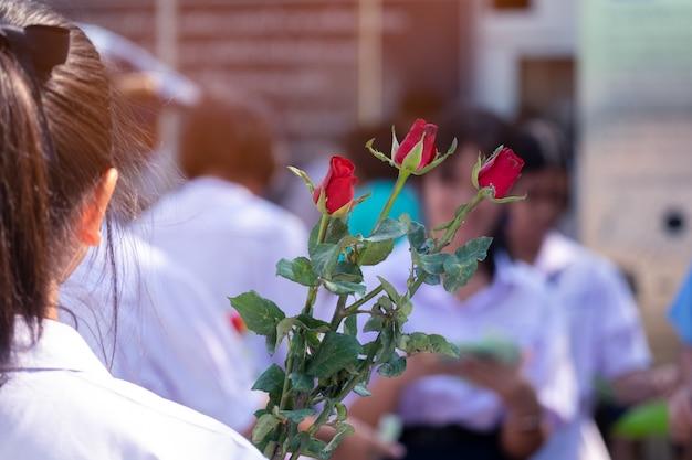Aziatische middelbare scholieren houden rozen vast voor haar vrienden