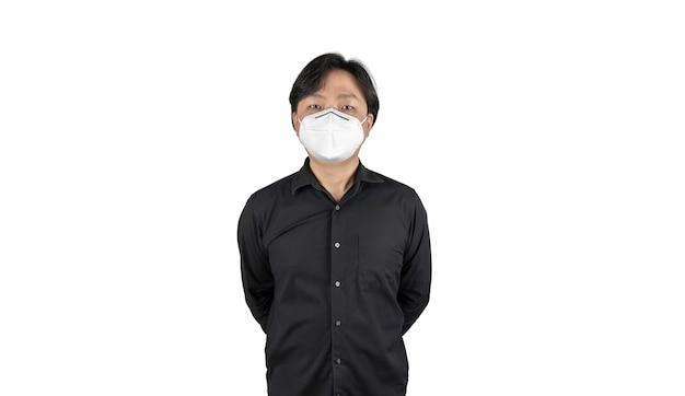 Aziatische middelste man in een zwart shirt draagt een wit masker staat voor een witte heldere achtergrond